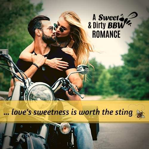 A handsome, powerful, bearded biker embraces the lovely blonde seated behind him on his Harley motorcycle, on a road through a forest.